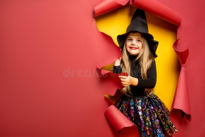 Skratta den roliga barnflickan i en häxadräkt i halloween arkivbild