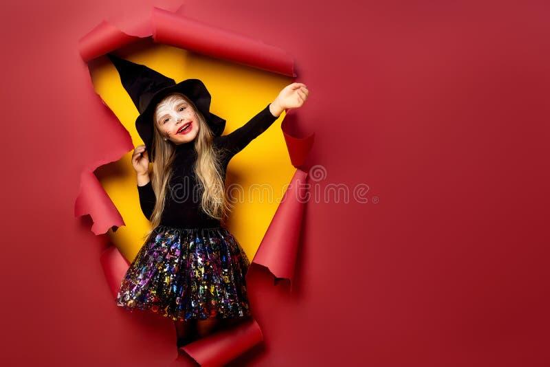 Skratta den roliga barnflickan i en häxadräkt i halloween royaltyfria foton