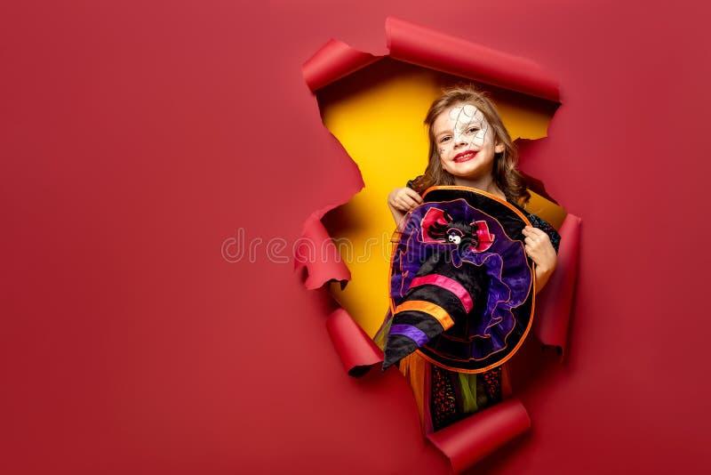 Skratta den roliga barnflickan i en häxadräkt i halloween royaltyfri fotografi