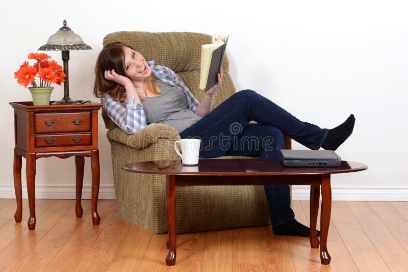 Skratta den tonåriga flickan med boken royaltyfri foto