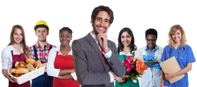 Skratta den turkiska affärsdeltagaren i utbildning med gruppen av latinska och afrikanska lärlingar fotografering för bildbyråer