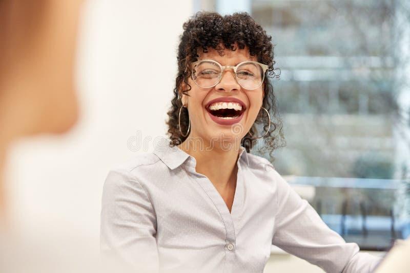 Skratta den unga den affärskvinnan eller studenten royaltyfri bild
