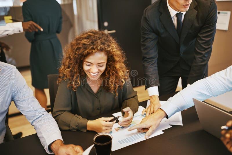 Skratta den unga affärskvinnan som diskuterar grafer med kontorscolle royaltyfri foto
