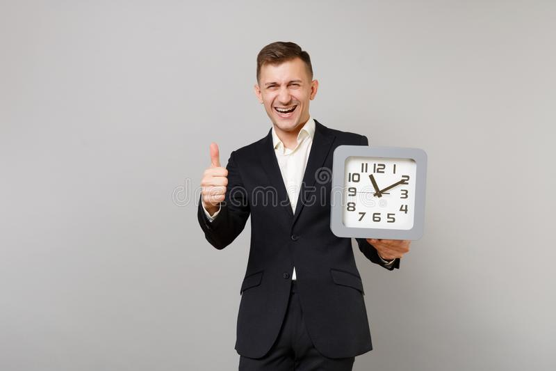 Skratta den unga affärsmannen i klassisk svart dräkt, vit skjorta som rymmer den fyrkantiga klockan som visar tummen som isoleras royaltyfri fotografi