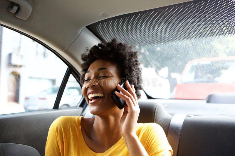 Skratta den unga kvinnan i en bil som talar på mobiltelefonen royaltyfria foton