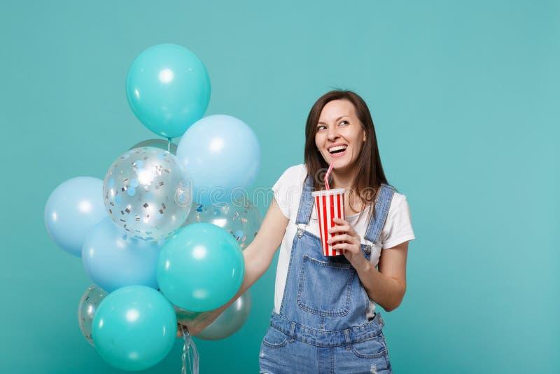 Skratta den unga kvinnan i grov bomullstvillkläder som rymmer den plast- koppen av cola eller sodavatten som firar med färgrika l arkivbild