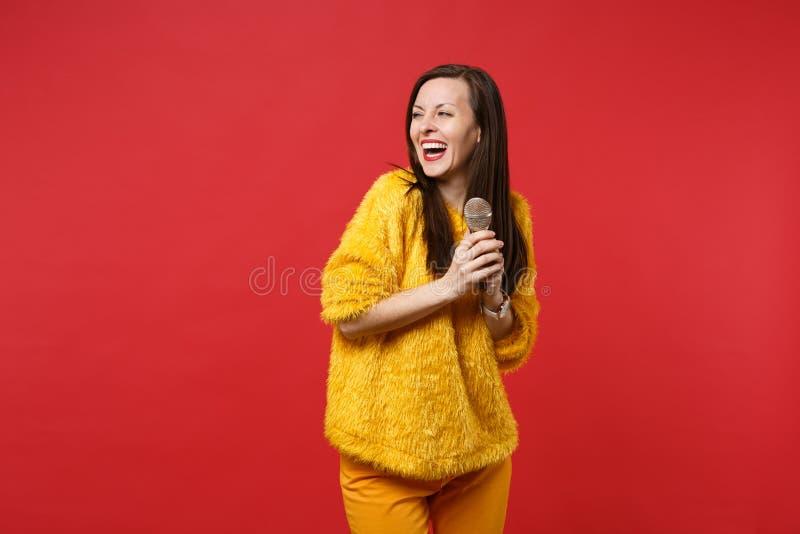 Skratta den unga kvinnan i den gula pälströjan som åt sidan ser för att sjunga sången som rymmer mikrofonen isolerad på den ljusa arkivbild