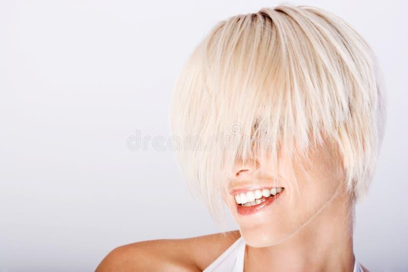 Skratta den unga kvinnan med kort blont hår arkivfoto