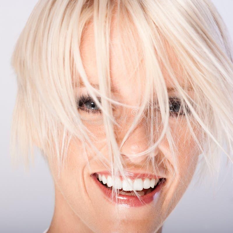 Skratta den unga kvinnan med skraj blont hår royaltyfri fotografi