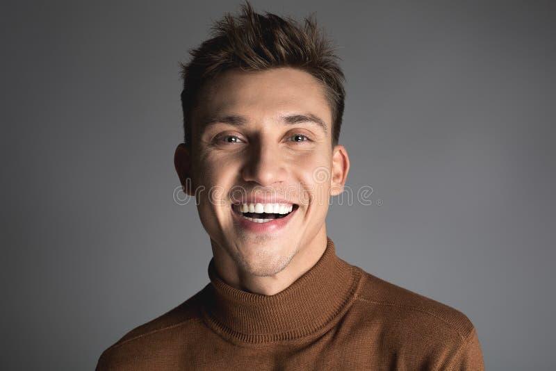 Skratta den unga mannen med attraktivt leende royaltyfria bilder