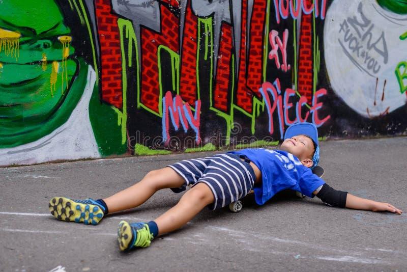 Skratta den unga pojken med hans skateboard fotografering för bildbyråer