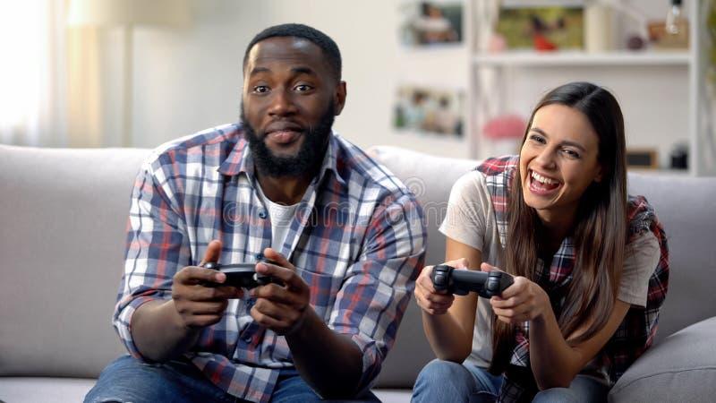 Skratta denlopp familjen som har roligt och att spela videospelet hemma, fritid arkivfoto