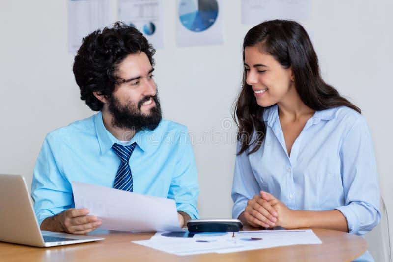 Skratta det arabiska affärslaget på arbete på skrivbordet arkivfoton