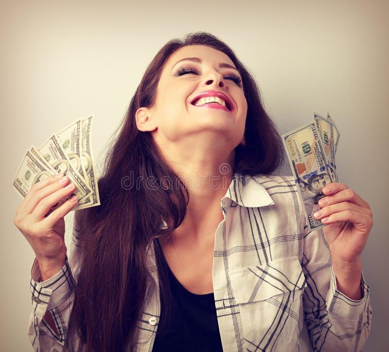 Skratta dollar för ung kvinna för vinnare hållande med stängda ögon Till royaltyfri foto