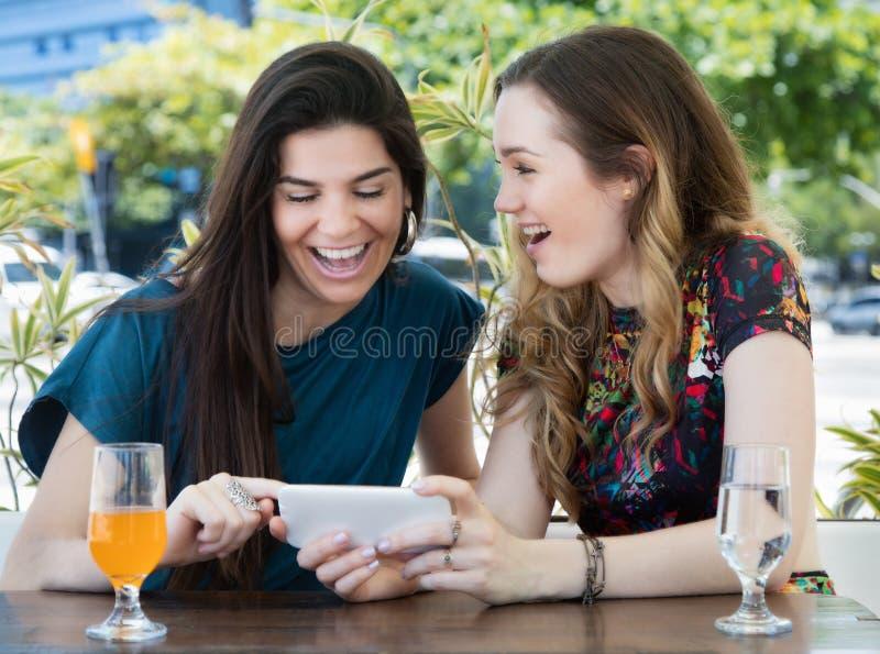 Skratta europeisk kvinna som två ser telefonen på restaurangen royaltyfri fotografi