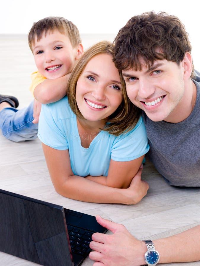 skratta för bärbar dator för familj lyckligt royaltyfri fotografi