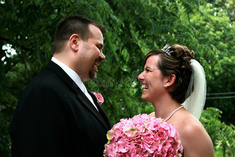 Skratta för brud och för brudgum royaltyfri foto