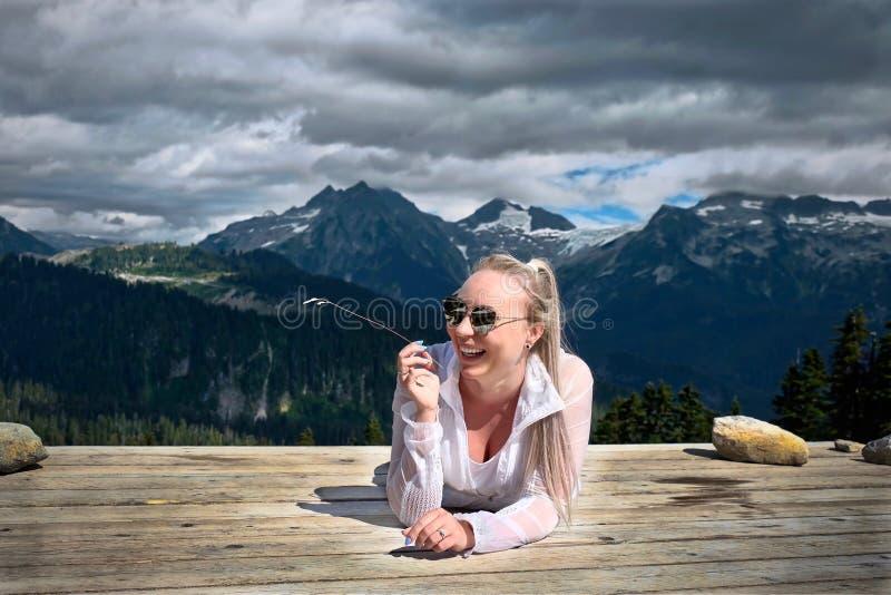 Skratta för kvinna Att ta för fotvandrare för ung dam vilar i tältplats royaltyfri bild