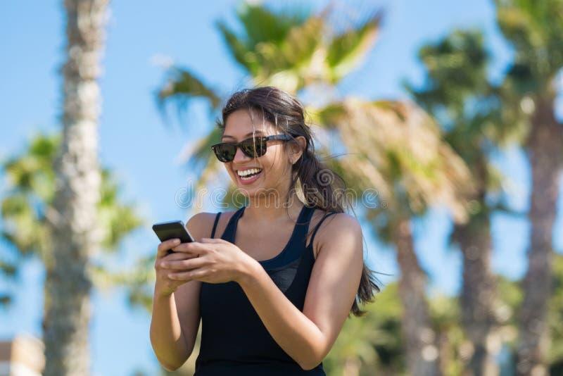 Skratta för mobiltelefon för ung lycklig kvinna hållande royaltyfri fotografi
