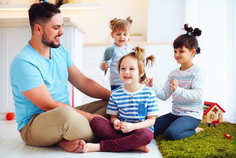 Skratta fadern med ungar som gör galna hårstilar hemmastadda arkivfoton