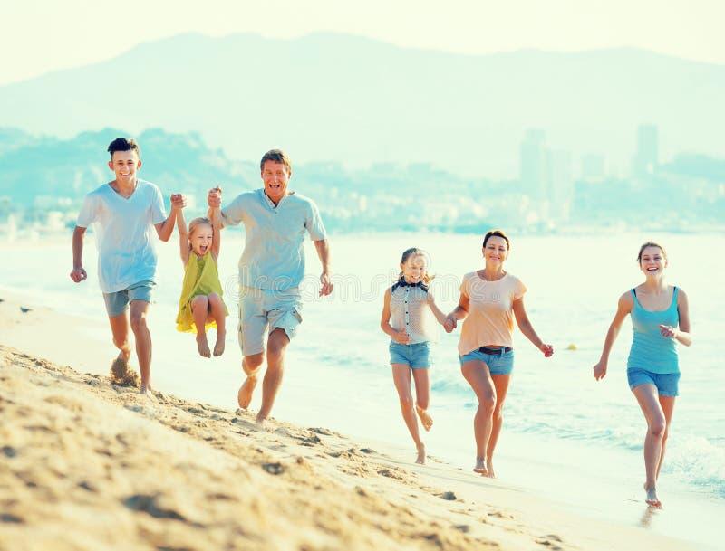 Skratta familjen med fyra barn som kör på stranden royaltyfri foto