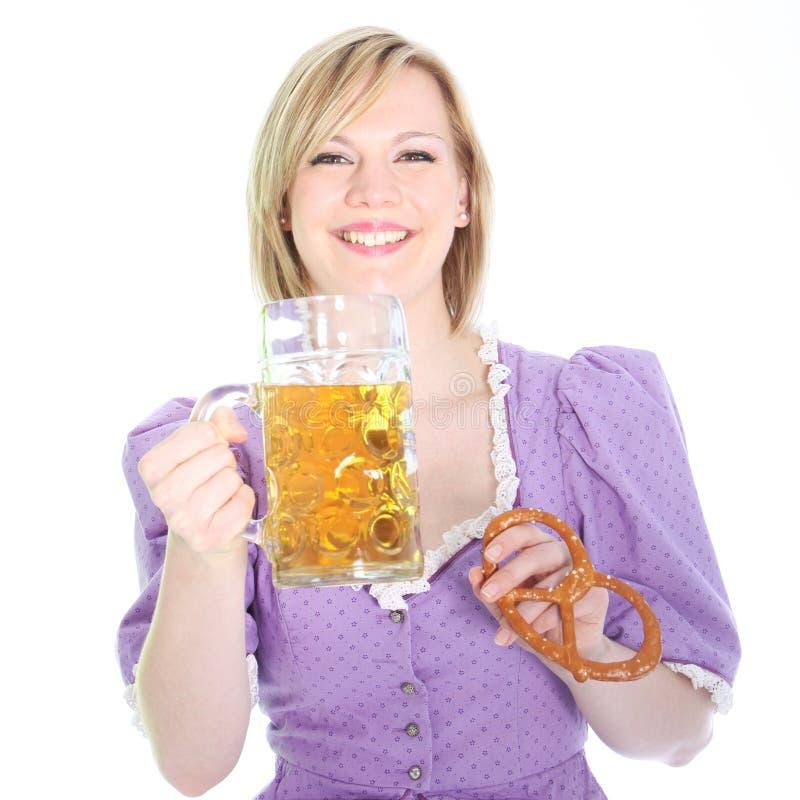 Skratta flicka med öl och en kringla arkivbild
