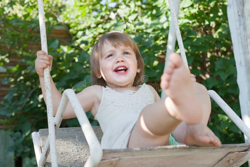 Skratta flicka på swing i sommar fotografering för bildbyråer