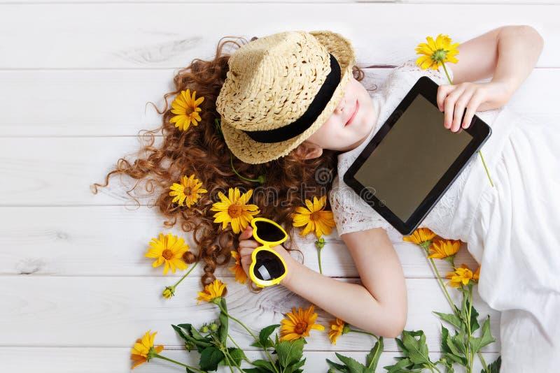 Skratta flickan i en sugrörhatt som vilar på minnestavlan i henne händer arkivfoton