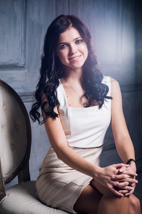 Skratta flickan i ett elegant vitt klänningsammanträde på en stol och le Effekt för Lens signalljuskonst arkivbilder
