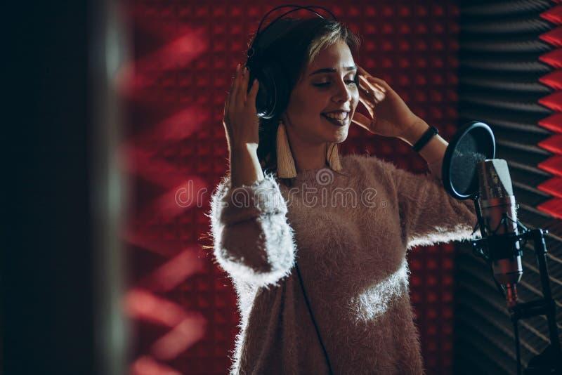Skratta flickan i hörlurar i studion royaltyfri foto