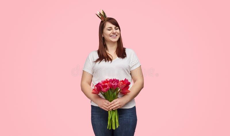 Skratta flickan i krona med ferieblommor royaltyfria foton