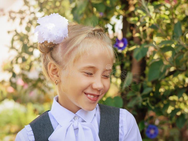 Skratta flickan i skolalikformig med en pilbåge på hennes huvud i hösten parkera royaltyfria bilder