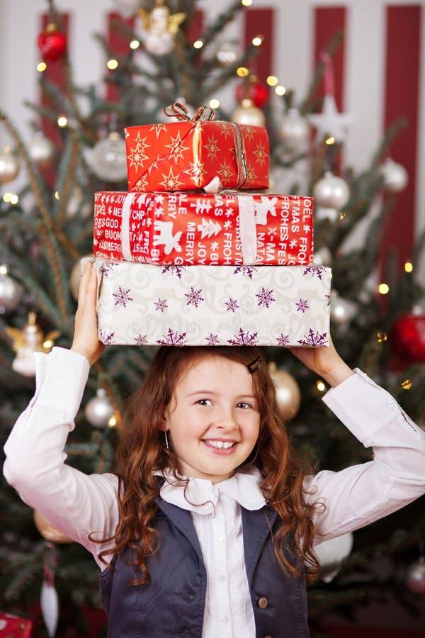 Skratta flickan med julgåvor på hennes huvud royaltyfri bild