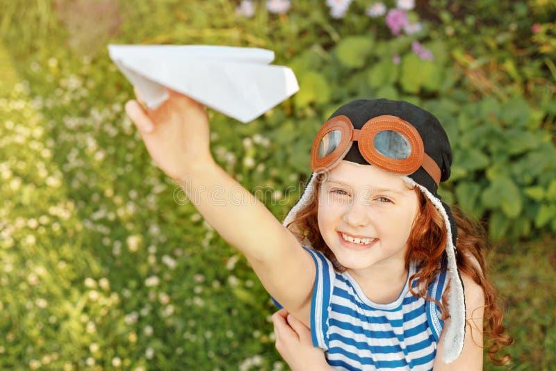 Skratta flickan som spelar med det pappers- flygplanet royaltyfria bilder