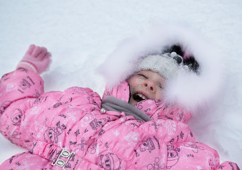 Skratta flickan som utanför ligger i snön, vinter arkivfoto