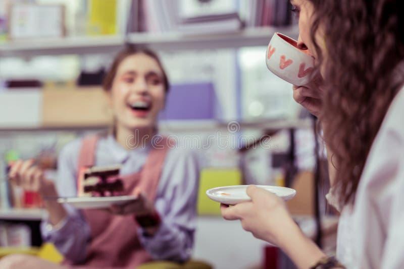 Skratta gladlynta damer som dricker te och att äta efterrätten royaltyfri fotografi