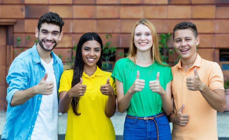 Skratta gruppen av fyra unga vuxna m?nniskor av utveckling y som visar tummar arkivfoton