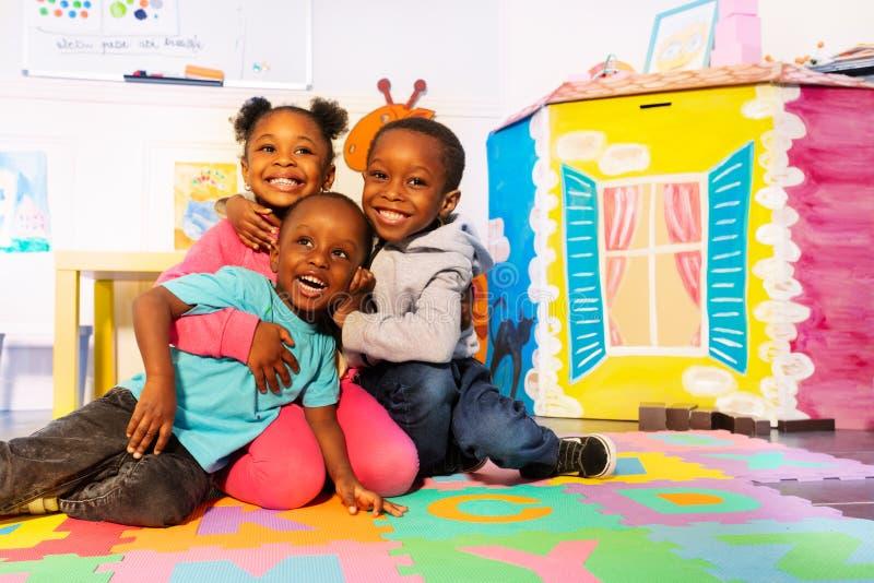 Skratta gruppen av ungelek på golvet i rum arkivbilder