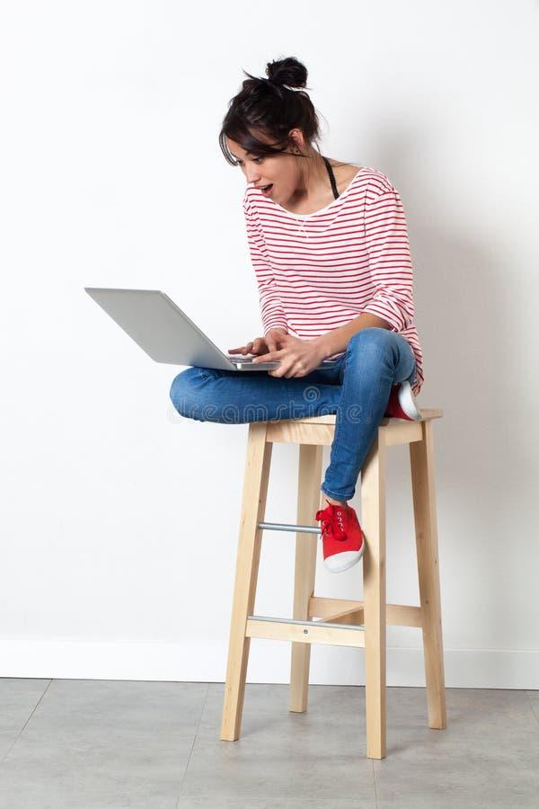 Skratta härlig meddelande överraskning för ung kvinna till och med hennes bärbar dator royaltyfri bild