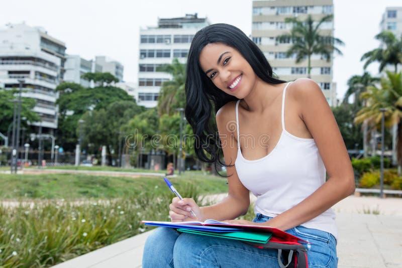Skratta infödd latin - amerikansk kvinnlig student som utomhus lär royaltyfri fotografi