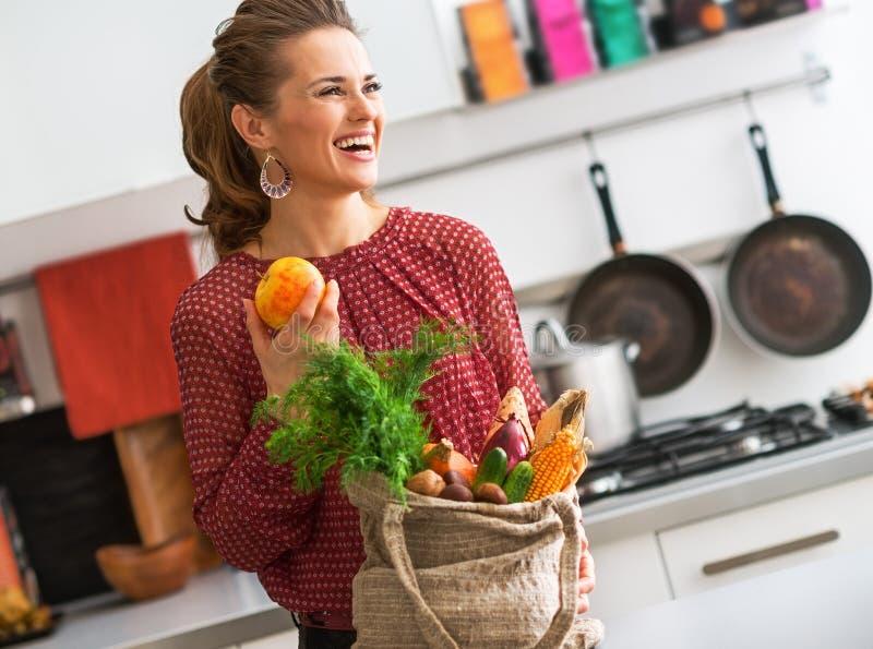 Skratta kvinnan i profil, nedgångfrukt och grönsaker i kök arkivbilder