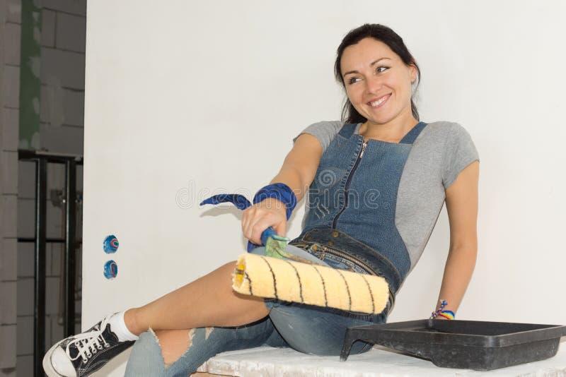 Skratta kvinnan med en målarfärgrulle arkivbilder