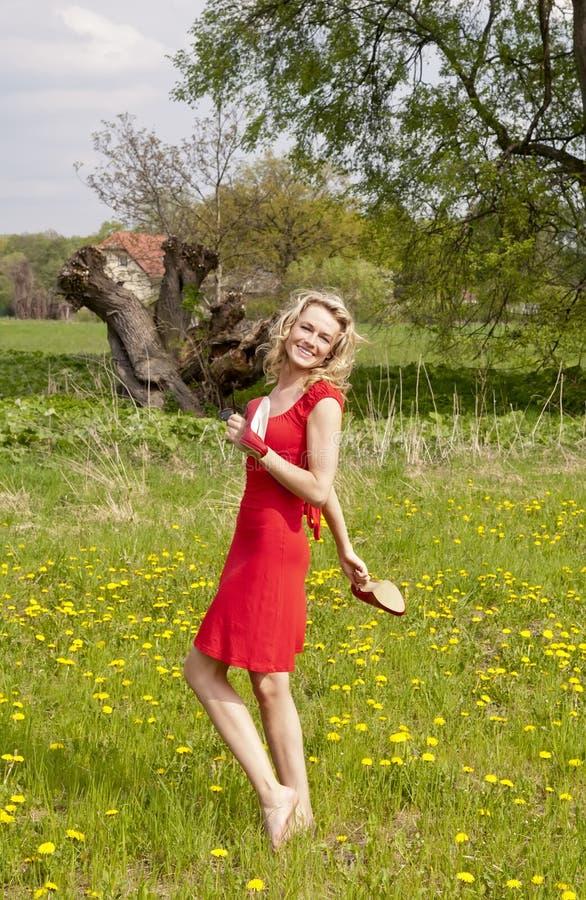Skratta kvinnan med höga häl i en äng arkivfoto