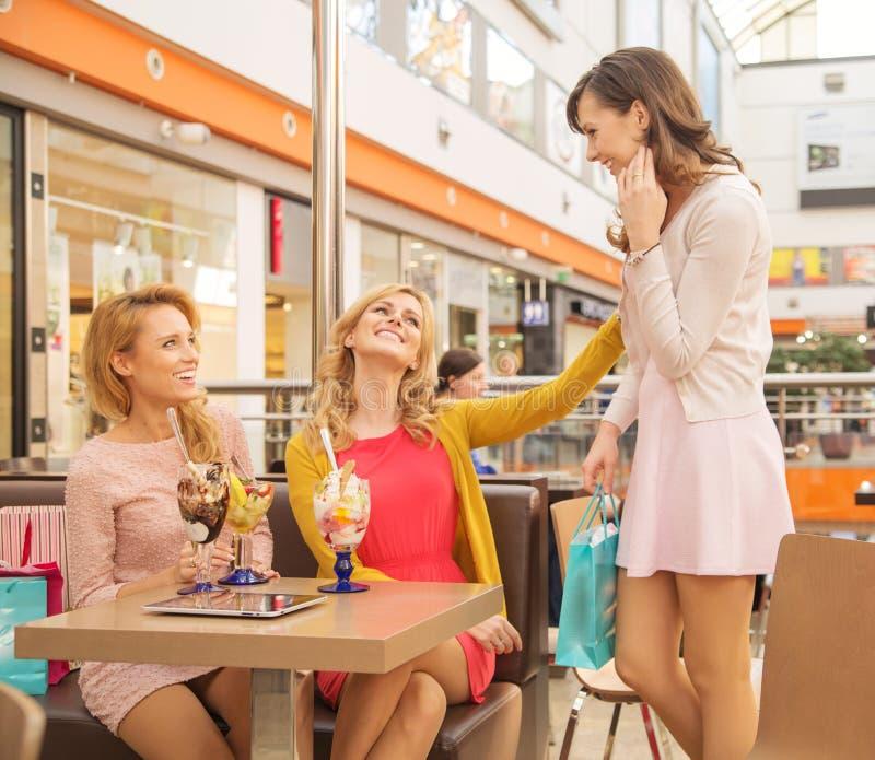 Skratta kvinnliga vänner i shoppinggalleriakafét arkivfoto