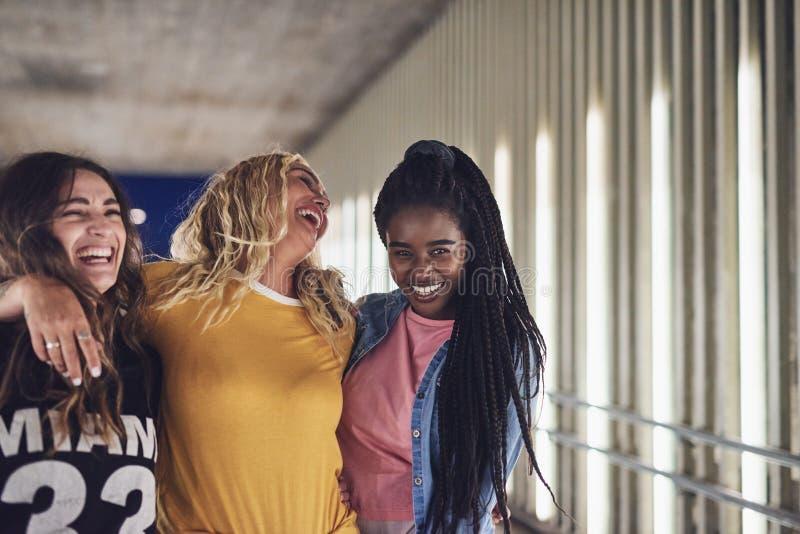 Skratta kvinnliga vänner som tillsammans går i staden på natten arkivbild