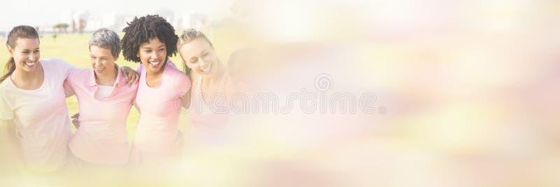 Skratta kvinnor som bär rosa färger för bröstcancer arkivbilder