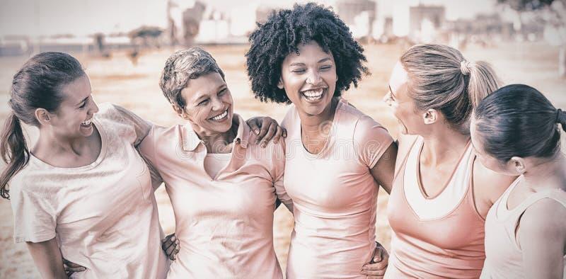 Skratta kvinnor som bär rosa färger för bröstcancer arkivfoton