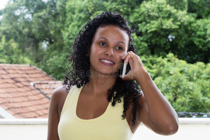 Skratta latin - amerikansk kvinna med svart hår på telefonen royaltyfri foto