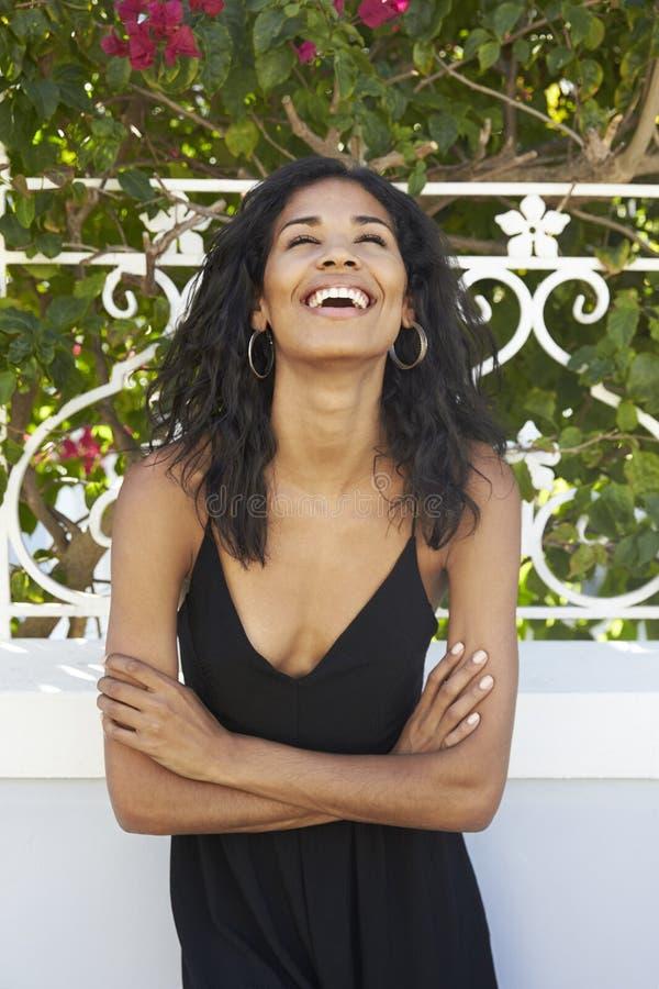 Skratta latin - amerikansk kvinna utomhus med korsade armar fotografering för bildbyråer