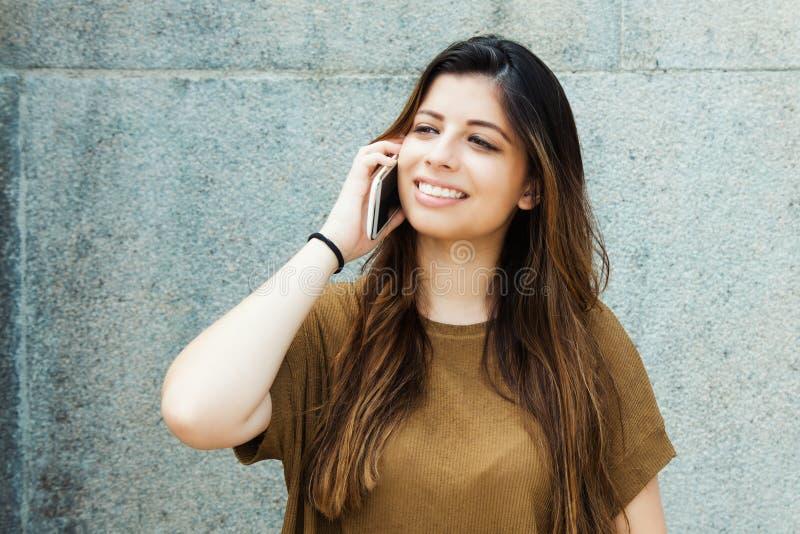 Skratta latin - amerikansk ung vuxen kvinna som talar på mobil phon royaltyfri foto